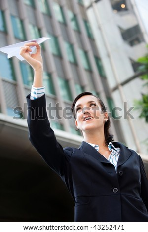 An attractive young businesswoman holding a paper plane against city backdrop