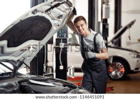An attractive young car mechanic is smiling: car service and mai #1146451091