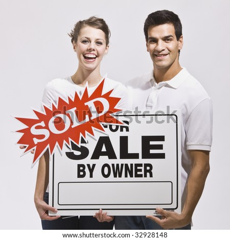 An attractive young couple holding a real estate sign with a 'sold' sticker on it.  They are smiling directly at the camera and look excited. Square.