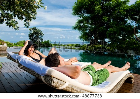 An attractive young couple in swimwear relaxing by the pool outdoors