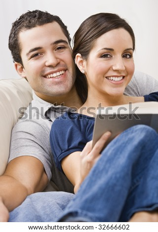 An attractive young couple relaxing together.  The female is holding a book and they are smiling directly at the camera. Vertically framed photo.