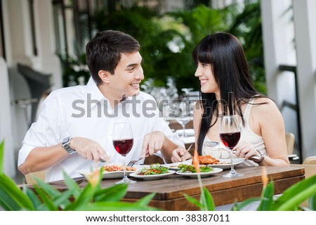 An attractive young couple shares a salad at an outdoor restaurant