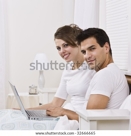 An attractive young couple sitting in bed together and holding a laptop.  They are smiling into the camera and are both wearing white. Square framed photo.