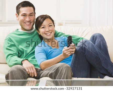 An attractive young couple sitting on a couch and watching television.  They are smiling directly at the camera.  The female is holding a remote.  Horizontally framed photo.