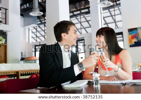 An attractive young couple toasting with white wine in a restaurant - stock photo