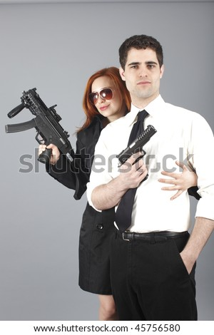 An attractive young couple with guns.