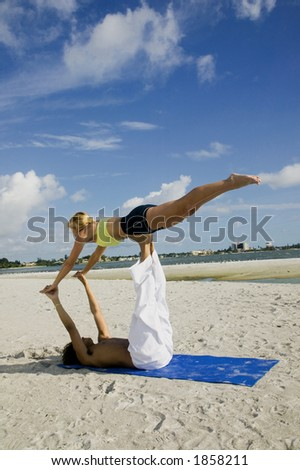 An attractive young couple works out on the beach