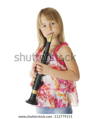 An attractive young elementary girl holding her clarinet, ready to play.  On a white background.
