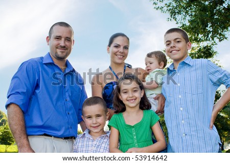 An attractive young family together at the park together on a nice spring or summer day.
