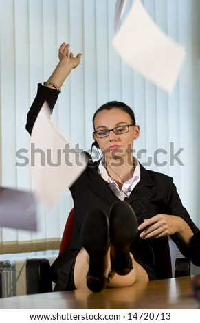 An attractive young female businesswoman throws a sheaf of papers into the air in frustrated resignation
