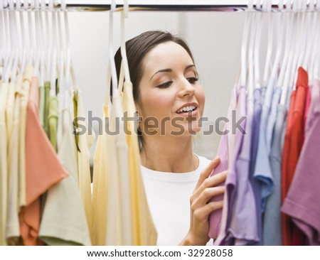 An attractive young female looking through a clothing closet.  She is smiling.  Horizontally framed photo.