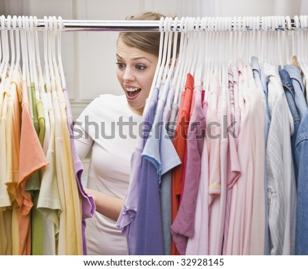 An attractive young female looking through clothing in a closet.  She has an excited expression on her face.  Vertically framed photo.