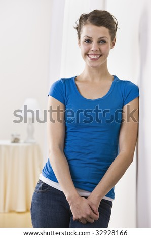 An attractive young female smiling directly at the camera.  Vertically framed photo.