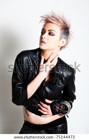 An attractive young female wearing punk fashion looks to the side with a blank expression. Vertical shot.