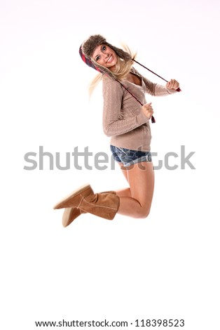 An attractive young female woman with long blond hair wearing boots and shorts jumping into the air against white background