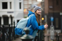 An attractive young girl in a blue jacket, gray hat and blue backpack walks along the bridges of Amsterdam. Traveler girl enjoys the views of the city.