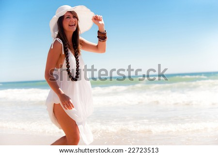 An attractive young girl posing with a cool hat on the beach
