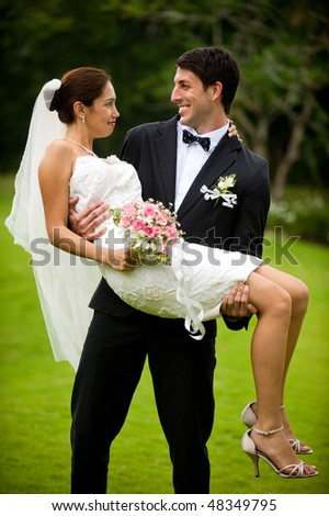 An attractive young groom carrying his bride in a garden outdoors