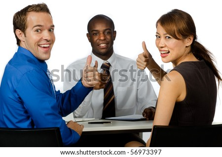 An attractive young group of business professionals giving the thumbs up in their office against white background