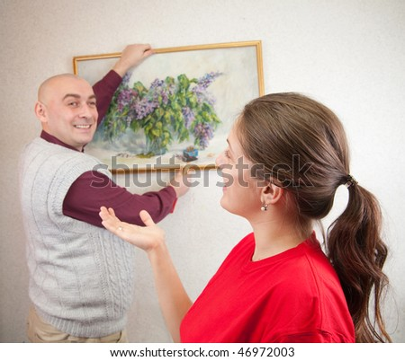 An attractive young man and his wife attempting to hang an art picture. Focus on girl