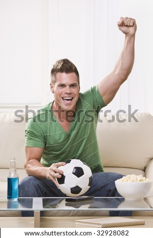 An attractive young man holding a soccer ball and cheering with his fist in the air.  He is looking directly at the camera. Vertically framed photo.