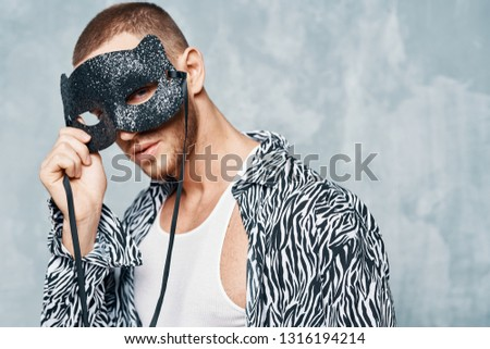 An attractive young man holds a masquerade mask in front of his eyes, a black-and-white shirt and a short tank top