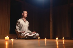 An attractive young man in a cotton gray dress for the practice of sitting in the lotus position in a dark room by candlelight and practicing meditation. Zen like practice