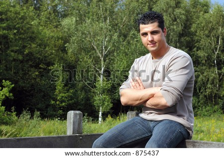 An attractive young man on his lunch hour, taking a rest in the park, sitting on a fence.