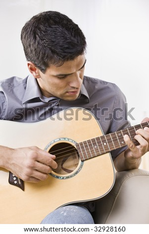 An attractive young man playing the acoustic guitar.  He is looking down at the guitar.  Vertically framed shot.