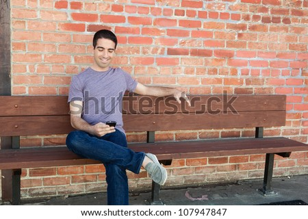 An attractive young man sitting on a bench outside using his cell phone wearing a purple shirt and jeans.