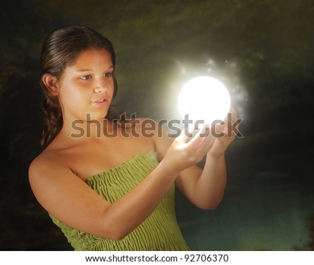 An attractive young teen enchanted by a glowing mystic ball in a dark environment.