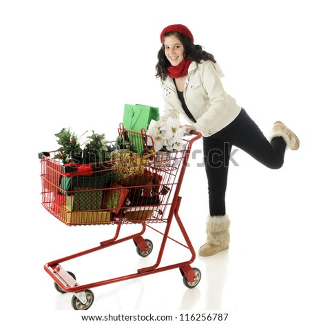 An attractive young teen running with a shopping cart filled with Christmas goodies.  On a white background.