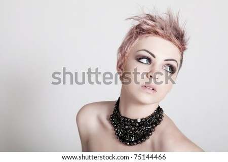 An attractive young topless female with a serious expression is wearing a necklace and looking down. Horizontal shot.