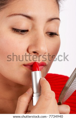 An attractive young woman applying red lipstick
