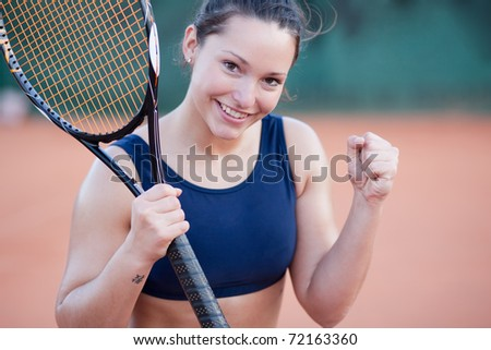 An attractive young woman celebrating after winning a tennis match