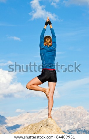 An attractive young woman doing a yoga pose for balance and stretching high in the mountains