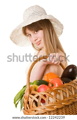 An attractive young woman holding a basket of delicious fresh vegetables. Isolated on white.