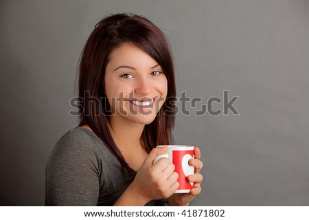 An attractive young woman holding a warm cup of coffee, tea or cocoa