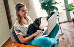 An attractive young woman in glasses is working on a laptop while sitting cross-legged in a comfortable chair at home with a funny assistant cat on her legs.