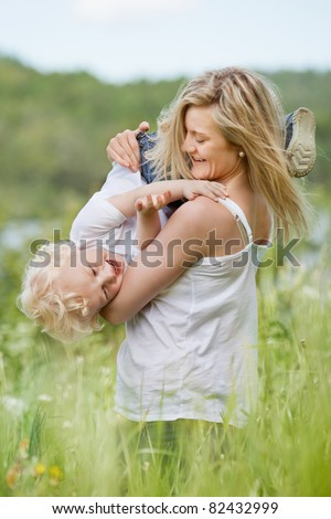 An attractive young woman playing with sweet little boy in green meadow