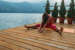 An attractive young woman practicing yoga outdoors during the day