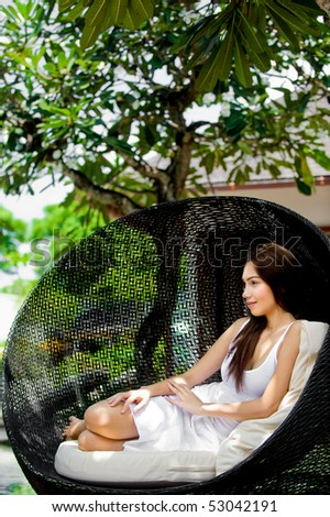 An attractive young woman relaxing and lounging outdoors