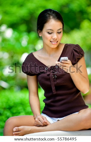 An attractive young woman using her mobile phone outdoors