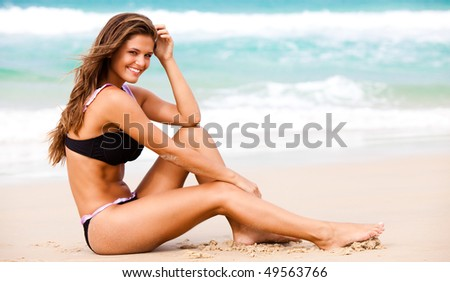 An attractive young woman wearing a black bikini sits on a beach with her elbow on her knee and her hand to her head.  Surf can be seen in the background. Horizontal shot.