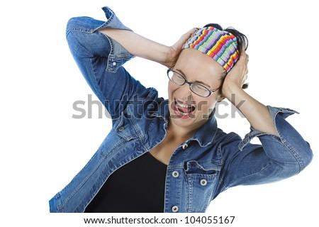 An attractive young woman with glasses, wearing black top, blue jeans, striped headband, is screaming with mouth wide open, pressing her hands to her temple - isolated on white