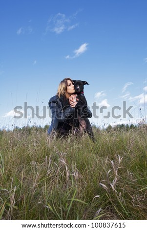 An attractive young woman with her black puppy in a field of long grass and sky.