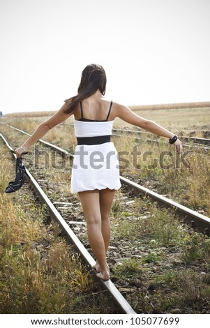 An attractive young woman with long brown hair blown by the wind, wearing a white mini dress and holding a black high-heel sandal in her left hand is walking bare feet on the railway