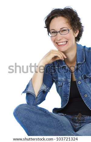An attractive young woman with short brown hair, wearing glasses, blue jeans, black top, sitting cross-legged, is laughing very happily - isolated on white