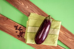 an aubergine, haricot beans and green towel on brown wood boards on green background