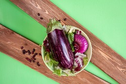 an aubergine, onion and lettuce on a green bowl and haricot beans on two brown wood boards on green background
